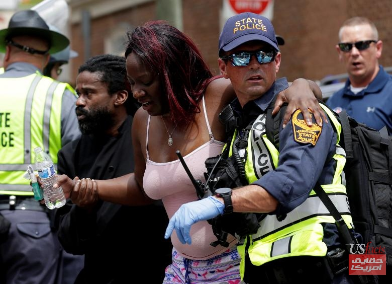 Rescue workers assist a victim who was injured when a car drove through a group of counter protestors at the
