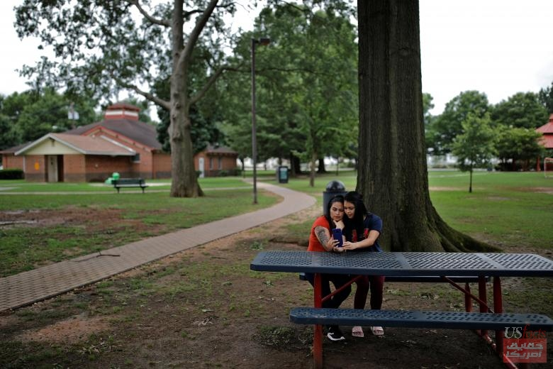 Isabela, an asylum seeker from El Salvador, and her 17-year-old daughter Dayana's sit on a park bench in Brentwood, Maryland