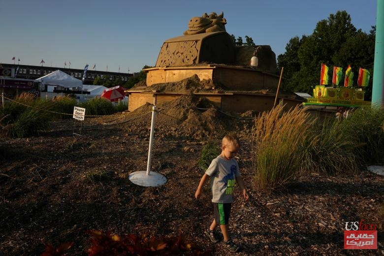 Brayden Faust of Des Moines walks past a sand sculpture at the Iowa State Fair in Des Moines