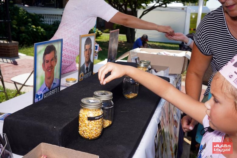 Mazzie Ferchen of Urbandale casts a vote for Iowa gubernatorial candidate Fred Hubbell at a corn kernel voting station at the Iowa State Fair in Des Moines