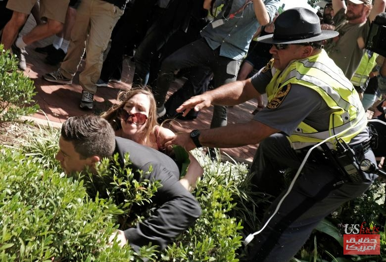 Jason Kessler is helped by police after being tackled by a woman after he attempted to speak at a press conference in front of Charlottesville City Hall in Charlottesville
