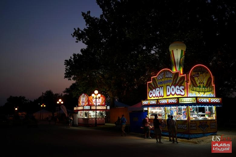 The sun sets behind a corn dog stand at the Iowa State Fair in Des Moines