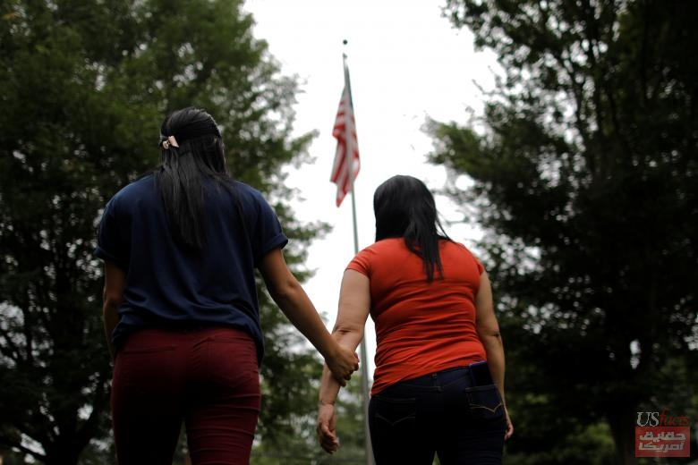 Isabela, an asylum seeker from El Salvador, holds her 17-year-old daughter Dayana's arm as they walk in a park next to a U.S. flag, several days after they were reunited following their separation at the U.S.-Mexico, in Brentwood