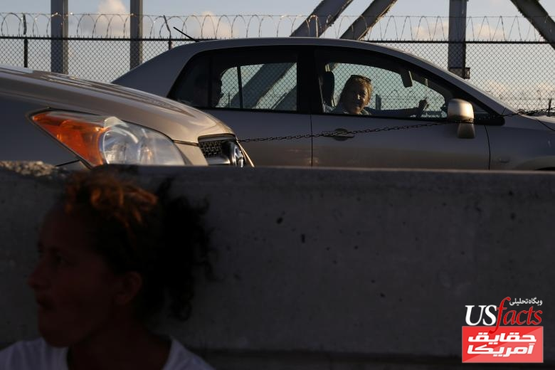 A Honduran woman seeking asylum waits on the Mexican side of the Brownsville & Matamoros International Bridge as cars pass by, after being denied entry by U.S. Customs and Border Protection officers near Brownsville