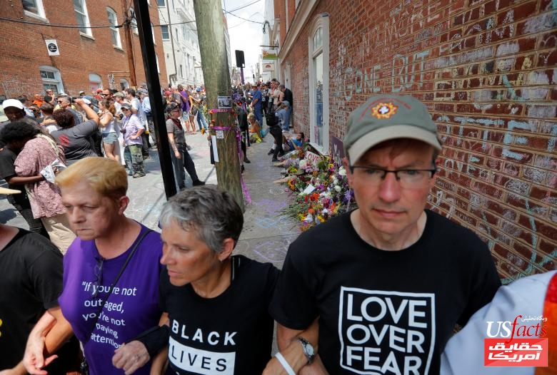 Demonstrators link arms at the site where Heather Heyer was killedin Charlottesville