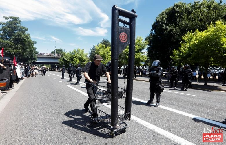 A counter-protester pushes a guillotine down the road during a rally by the Patriot Prayer group in Portland
