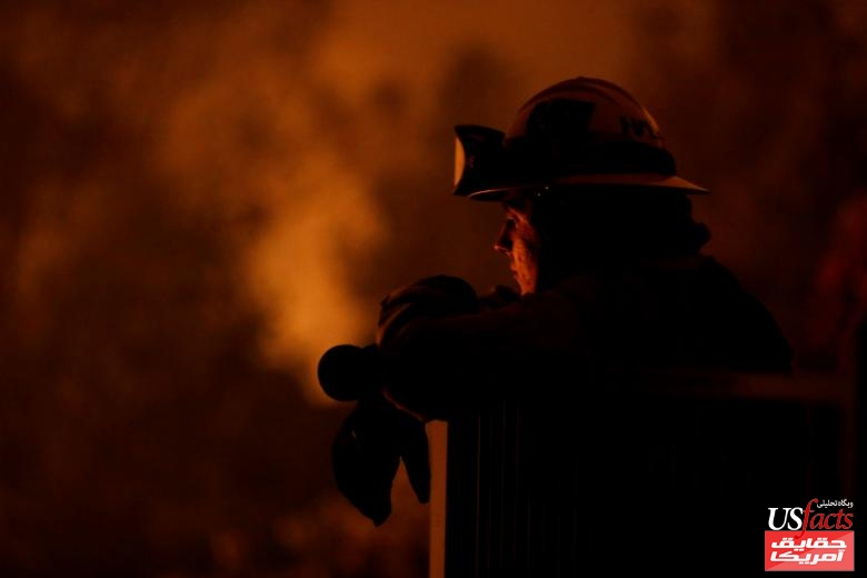 Cal Fire firefighter Zach Hallums watches as fire burns in a canyon below homes as crews battle the Carr Fire, west of Redding