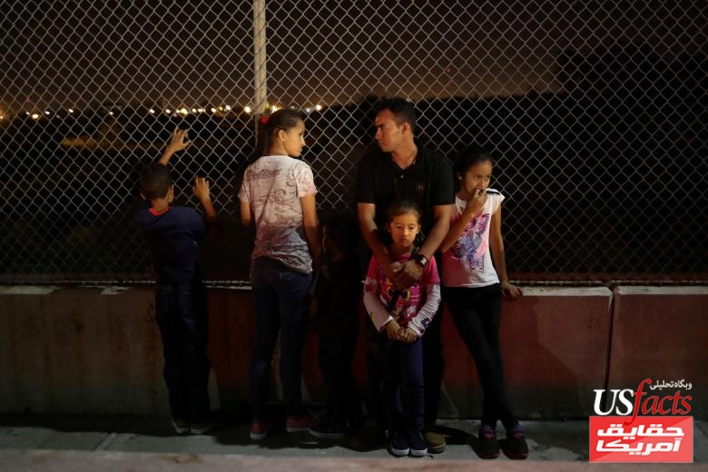 Asylum seekers wait on the Mexican side of the Brownsville & Matamoros International Bridge after being denied entry by U.S. Customs and Border Protection officers near Brownsville