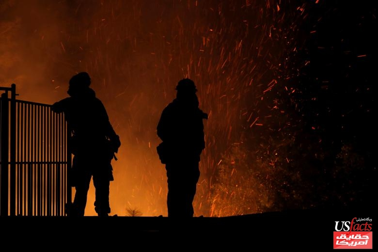 Burning embers swirl around firefighters as they stand guard at a home while battling the Carr Fire, west of Redding