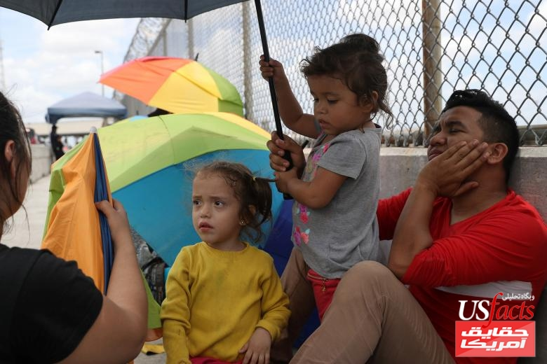 Honduran families seeking asylum wait on the Mexican side of the Brownsville-Matamoros International Bridge after being denied entry by U.S. Customs and Border Protection officers near Brownsville