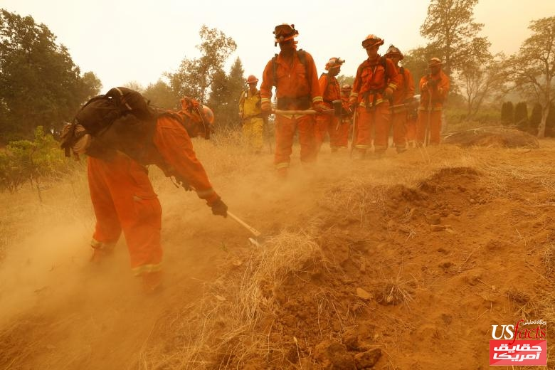 An inmate fire crew cuts fire lines in hot and smoky conditions while working to stop the spread of the Carr Fire, west of Redding, California
