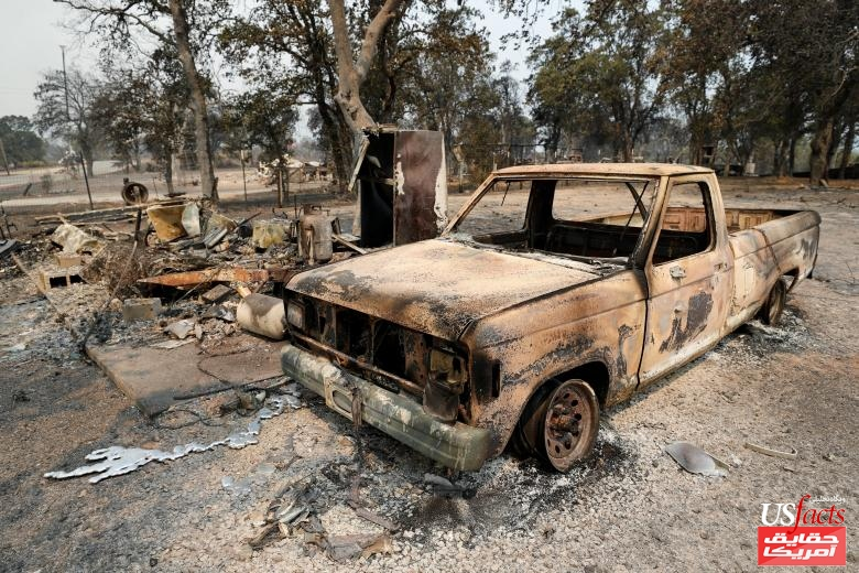 A burned truck sits next to a home that burned in the Carr Fire west of Redding