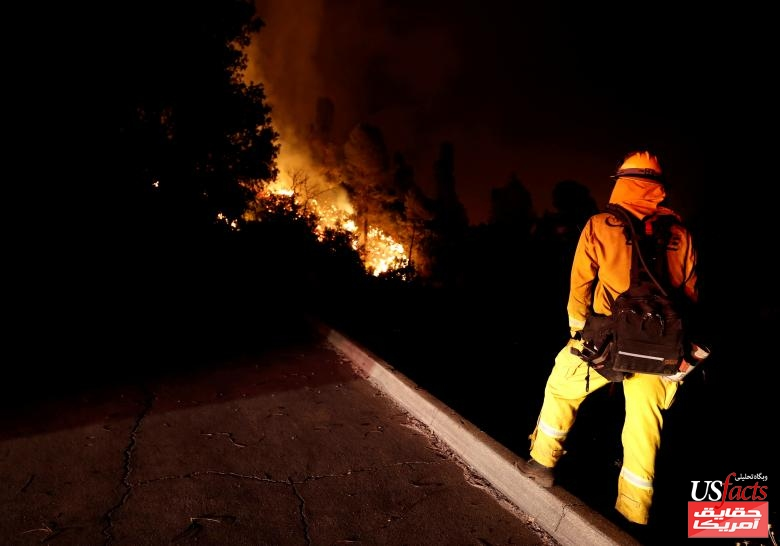 A firefighter watches the flames advance up a hill towards homes as crews battle the Carr Fire, west of Redding