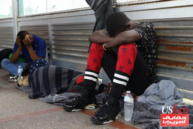 Asylum seekers from Guinea (R) and Honduras (L) wait on the Mexican side of the Brownsville-Matamoros International Bridge after being denied entry by U.S. Customs and Border Protection officers near Brownsville