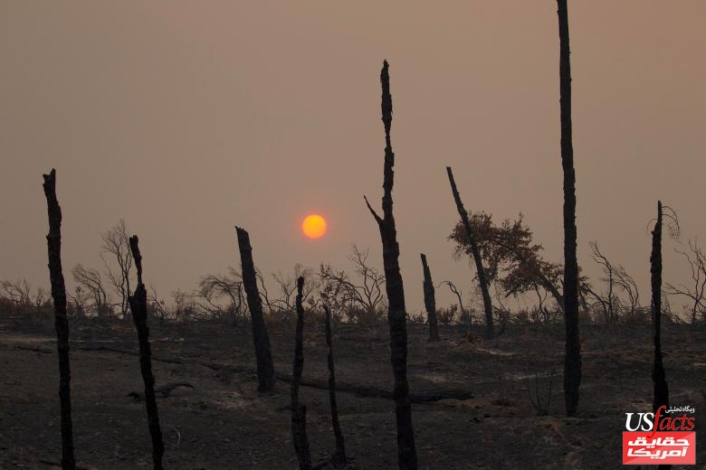 The sun sets over hills burned by the Carr Fire west of Redding