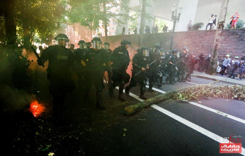 Police advance towards counter protesters during a rally by the Patriot Prayer group in Portland