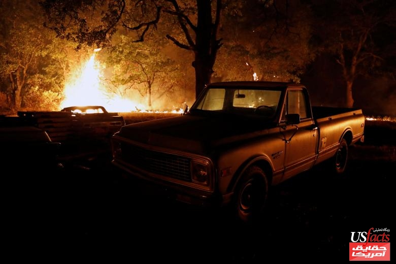 Flames of the Carr Fire approach a truck as it burns west of Redding
