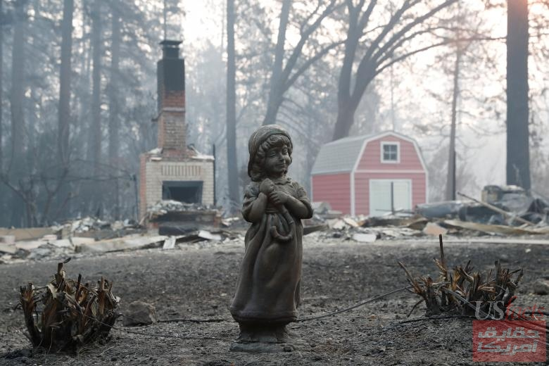 A statue stands in front of a home destroyed by the Camp Fire in Paradise