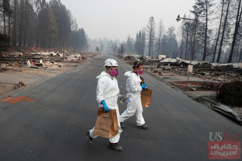 Forensic anthropologists Kyra Stull (C) and Tatiana Vlemincq (R) recover human remains from a trailer home destroyed by the Camp Fire in Paradise