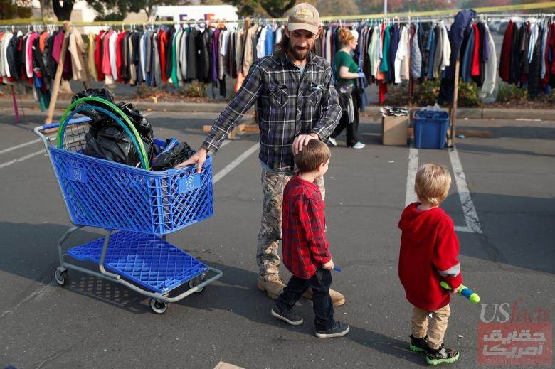 Justin Kraus, whose home in Paradise was destroyed by the Camp Fire, looks for toys for his sons, Liam, 5, (L) and Samuel, 3, at a donation site for evacuees in Chico