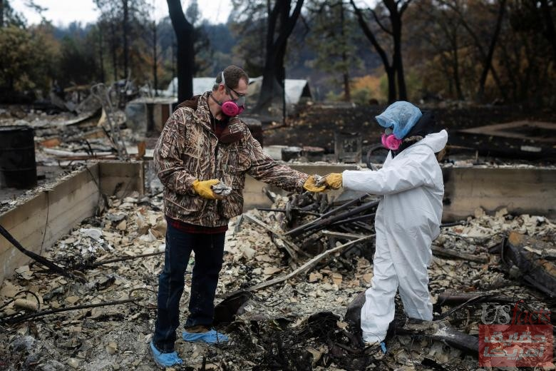 Vanthy Bizzle hands some small religious figurines to her husband Brett Bizzle in the remains of their home after returning for the first time since the Camp Fire forced them to evacuate in Paradise