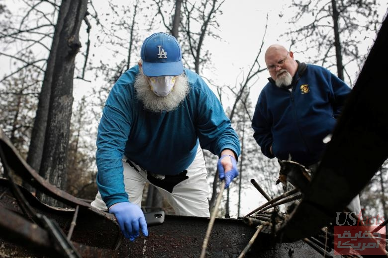 Stanley Miniszewski Sr. uses a burnt golf club to look for a pair of expensive dentures in the remains of his RV after returning for the first time since the Camp Fire forced him to evacuate as his friend Merrill Jackson looks on at Pine Ridge Park in Para