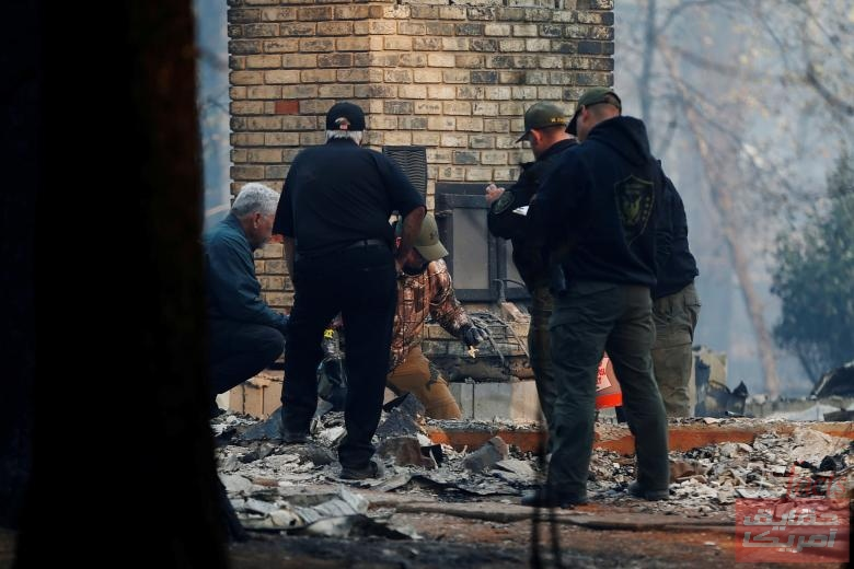 FILE PHOTO: Sheriff deputies retrieve remains of a deceased victim from a home during the Camp Fire in Paradise