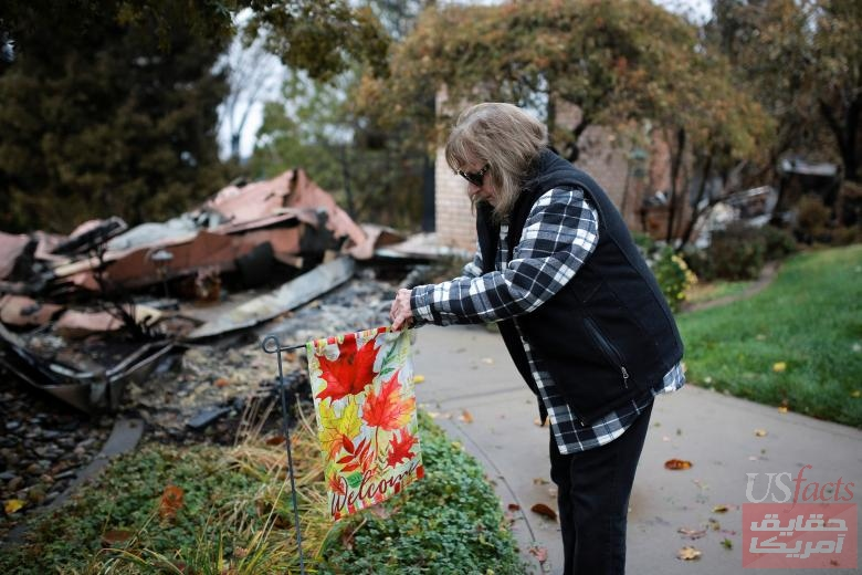 Gerryann Wulbern rehangs a welcome sign she found unburned on her lawn after returning to her home for the first time since the Camp Fire devastated the area in Paradise