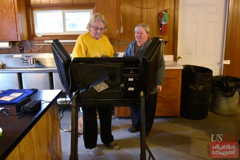 Poll worker Carol Bower shows Brenda Ruzic how to use the voting machine at the Rock Dam Rod and Gun Club in Foster Township, Wisconsin