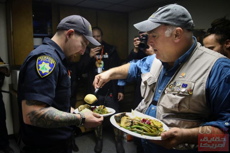 Jose Andres, chef and founder of World Central Kitchen, gives Paradise Police Department officer Tanner Ramlow a plate of Thanksgiving dinner at the Paradise Police Department in Paradise