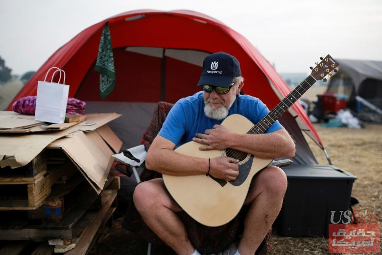 Kelly Boyer plays a guitar he was given outside his tent near Walmart after the Camp Fire destroyed his home in Paradise, in Chico, California