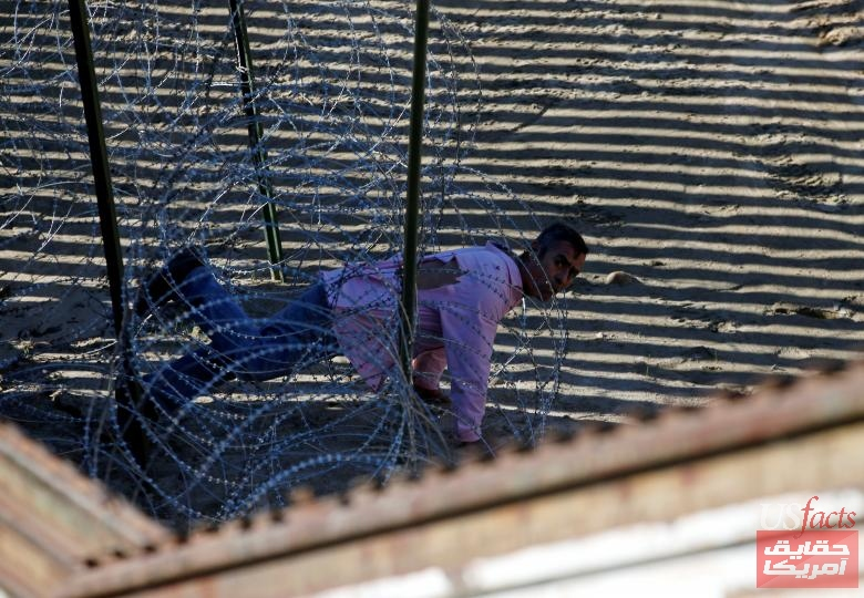 A migrant jumps the border fence and crawls through barbed wire to cross illegally from Mexico into the U.S. as pictured from Tijuana