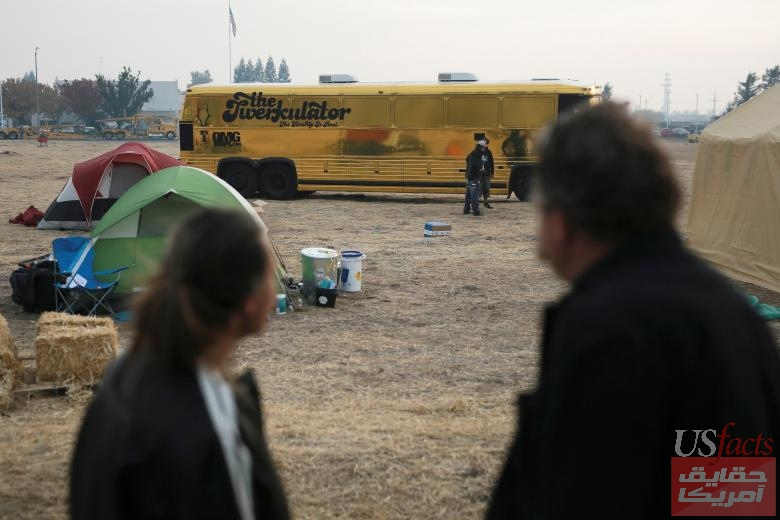 Camp Fire evacuees look at a bus titled 'The Twerkulator' that was equipped with laptops and wifi hotspots to assist people in signing up for FEMA assistance, in Chico, California