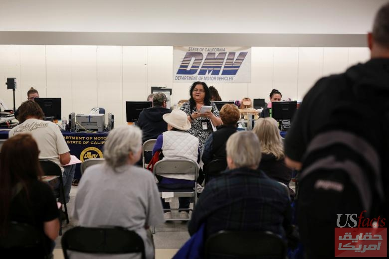 A woman helps Camp Fire evacuees get ID cards and driver's licenses at a makeshift DMV office inside the former Sears store in the Chico Mall in Chico, California