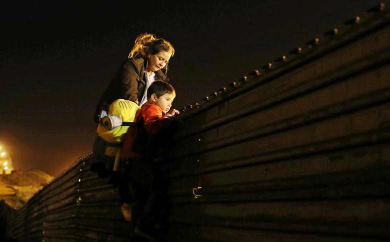 Migrants from Honduras, part of a caravan of thousands from Central America trying to reach the United States, jump a border fence to cross illegally from Mexico into the U.S., in Tijuana,
