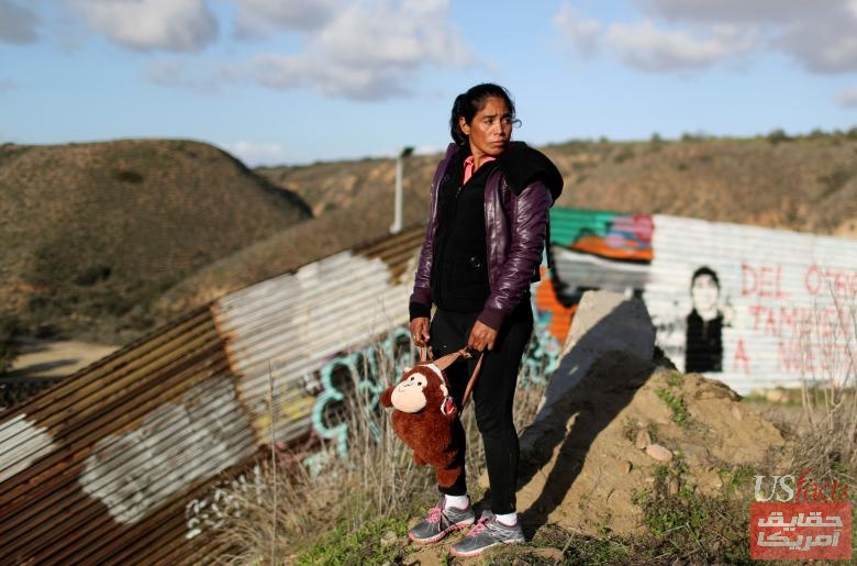 A Honduran woman looks towards her family, of a caravan of thousands from Central America trying to reach the United States, after her family jumped a border fence to cross illegally from Mexico into the U.S., in Tijuana,