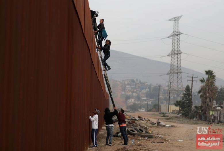 Migrants from Honduras, part of a caravan of thousands from Central America trying to reach the United States, climb a border fence to cross illegally from Mexico to the U.S., in Tijuana,