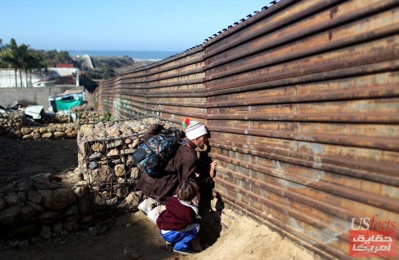 A migrant from Honduras, part of a caravan of thousands from Central America trying to reach the United States, looks through the border fence to cross illegally from Mexico to the U.S., in Tijuana
