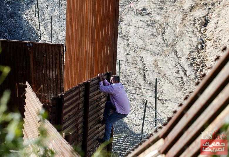 A migrant jumps the border fence to cross illegally from Mexico into the U.S. as pictured from Tijuana