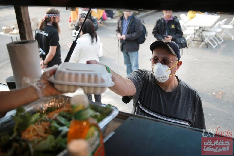 A man accepts a free hot meal in the former Toys-R-Us parking lot where volunteers are serving meals to Camp Fire evacuees and first responders, in Chico, California