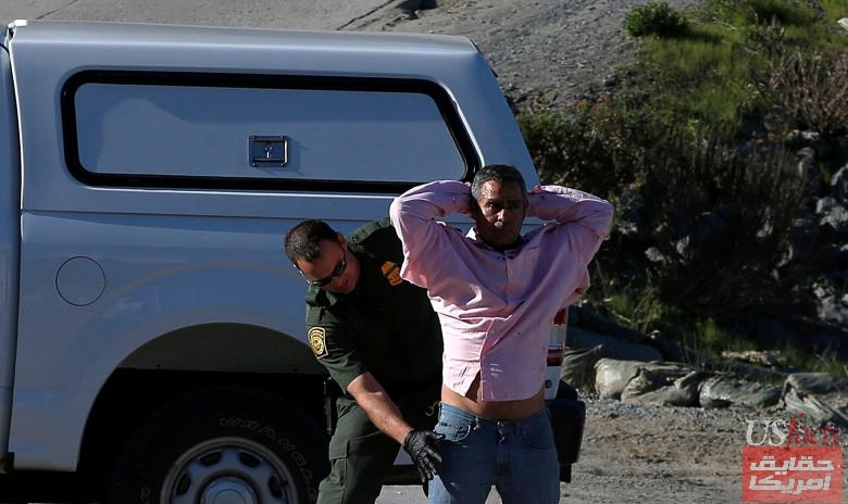 A U.S. CBP official detains a migrant who was trying to reach the United States at International Friendship Park, as photographed from Tijuana
