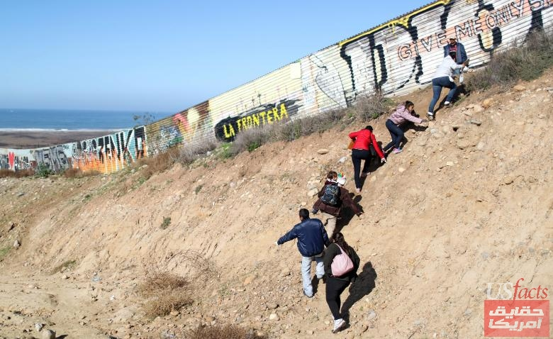 Migrants from Honduras, part of a caravan of thousands from Central America trying to reach the United States, walk next to the border fence as they prepare to cross it illegally, in Tijuana