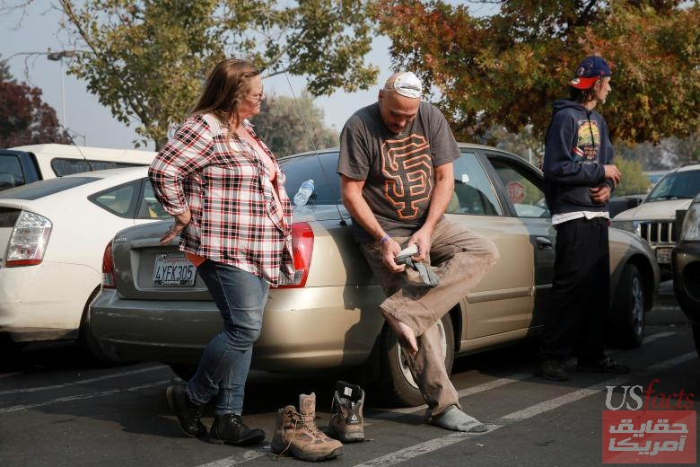 Mitchell Manley puts on socks his girlfriend Carol Daugherty (L) found him after the Camp Fire destroyed his home Concow, in Chico