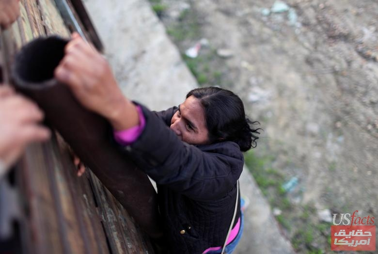 A migrant from Honduras, part of a caravan of thousands from Central America trying to reach the United States, jumps a border fence to cross illegally from Mexico into the U.S., in Tijuana,